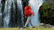 Female Hiker Reaching a Glacial Waterfall