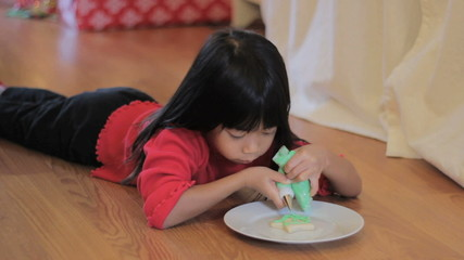 Girl Decorating Christmas Cookie With Green Icing