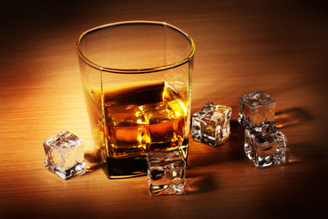 glass of scotch whiskey and ice on wooden table