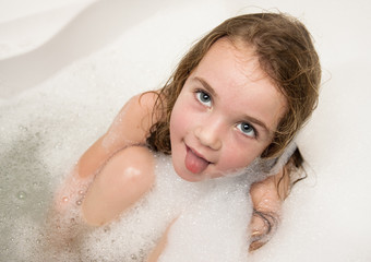 Little girl in soap foam