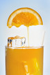 Fresh orange juice is flowing in a glass with ice