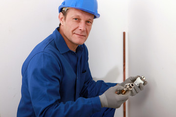 plumber showing plumbing pieces