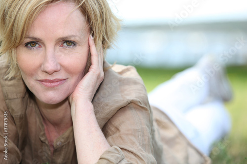 portrait of magnificent mature blonde lying on grass