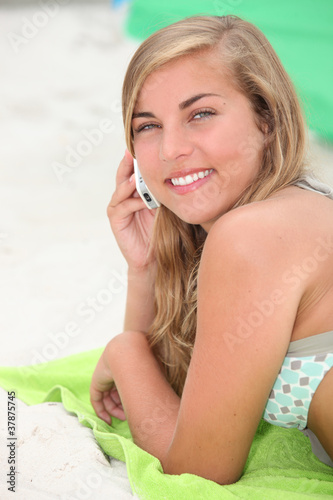 girl on the beach talking on her cell