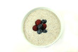 Bowl of chia cereal with berries on white background