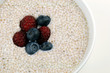 Close up of chia cereal with berries on white background