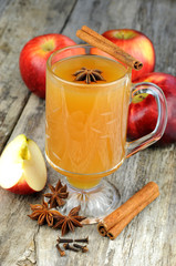 Fresh apple cider with spices, on rustic wooden background