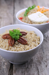 Bowls of quinoa salad on wooden background