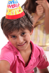 Young boy in a birthday party hat