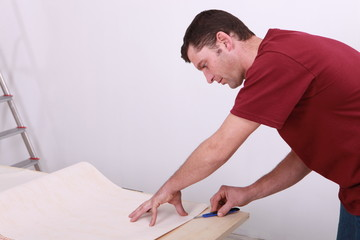 Tradesman cutting a sheet of paper