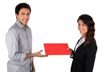 Woman handing folder to man