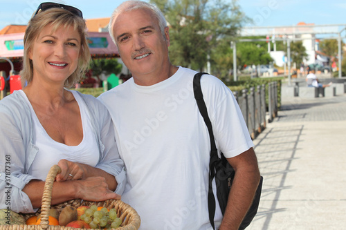 Couple on holiday with a basket of fruit