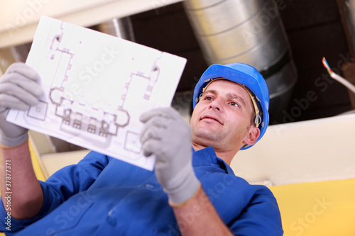 Man looking at plans for a heating installation