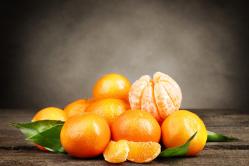 tangerines with leaves on wooden table on grey background