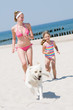 Happy summer vacation - girls playing with dog on the beach