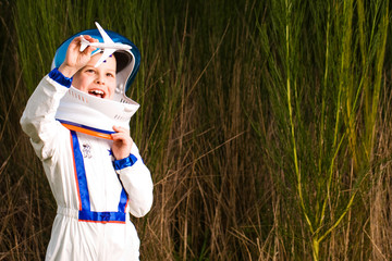 Young boy in an astronaut suit playing with toy airplane
