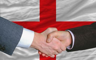 businessmen handshake after good deal in front of england flag