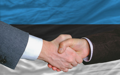 businessmen handshake after good deal in front of estonia flag