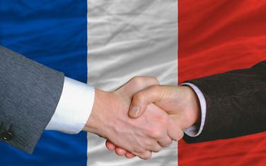 businessmen handshake after good deal in front of france flag