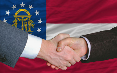 businessmen handshake after good deal in front of georgia flag