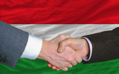 businessmen handshake after good deal in front of hungary flag