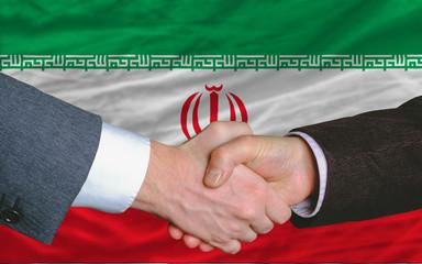 businessmen handshake after good deal in front of iran flag