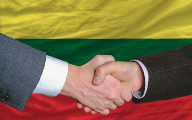 businessmen handshake after good deal in front of lithuania flag
