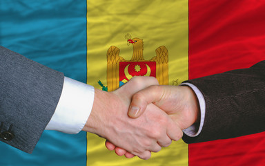 businessmen handshake after good deal in front of moldova flag