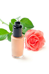 Closeup shot of foundation cream with a rose, on white