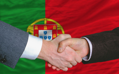 businessmen handshake after good deal in front of portugal flag