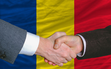 businessmen handshake after good deal in front of romania flag