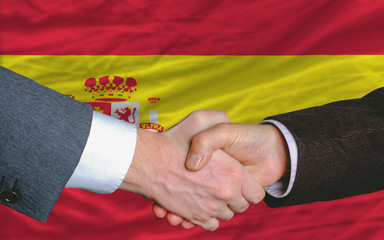 businessmen handshake after good deal in front of spain flag