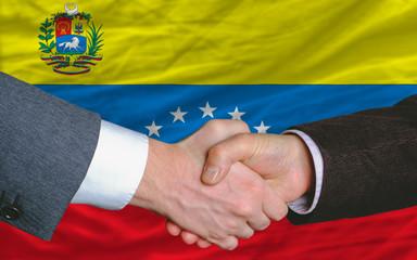 businessmen handshake after good deal in front of venezuela flag