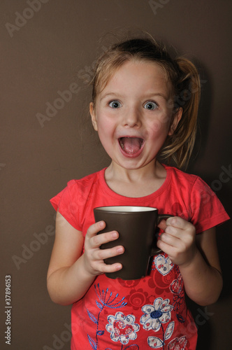 Surprised girl with brown cup