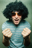 crazy young guy in afro curly wig with eyeglasses