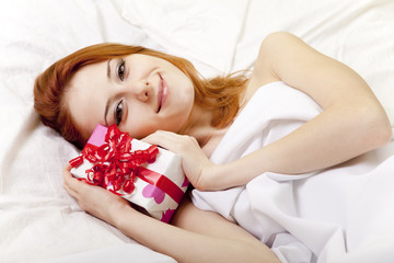 Red-haired girl in bed with gift