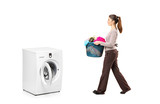 Female holding a laundry basket going towards a washing machine