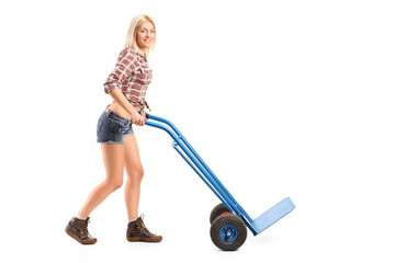 Female manual worker pushing an empty handtruck