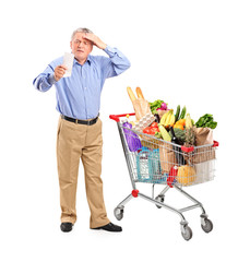 Shocked senior looking at store receipt next to a shopping cart