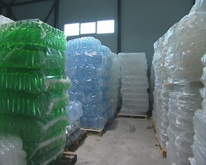 Piles of packaged PET bottles in warehouse.