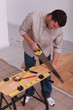 handyman cutting a board