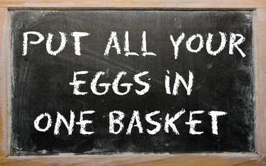 "Proverb ""Put all your eggs in one basket"" written on a blackboar"