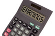 "Old calculator on white background showing text ""earnings"" in pe"