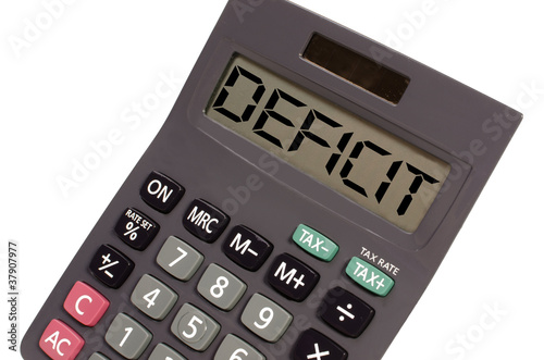"Old calculator on white background showing text ""deficit"" in per"