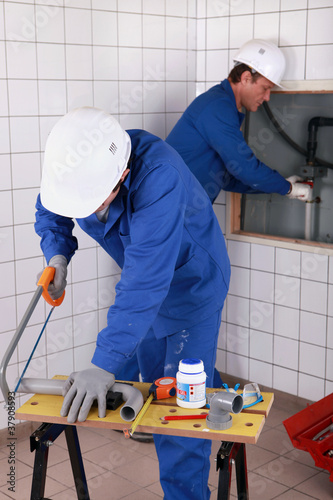 Two plumbers working