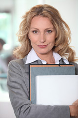 Businesswoman holding a file folder and a laptop