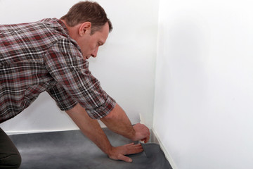 Man fitting linoleum flooring into the corner of a room