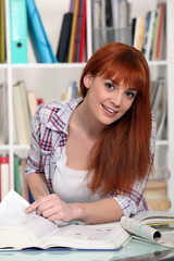 Young redhair student in the library.