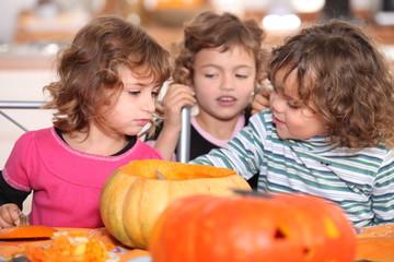 Kids preparing pumpkins for Halloween