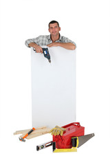 Man holding drill next to blank advertising panel